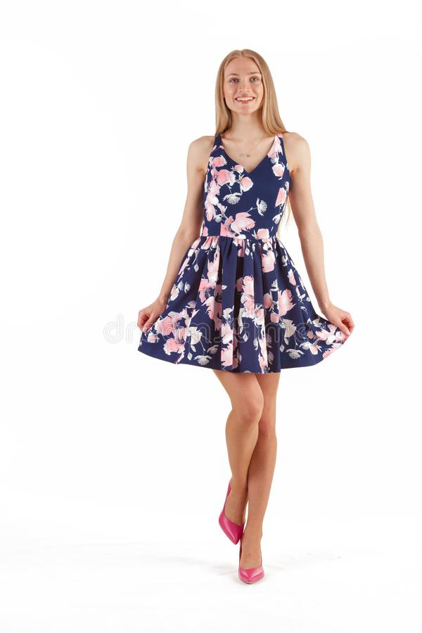 Beautiful young blonde woman in dark blue dress with floral print isolated on white background royalty free stock image