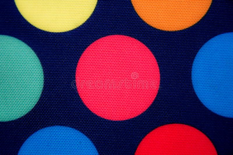 Dark blue fabric with colored circles. Background. texture stock image