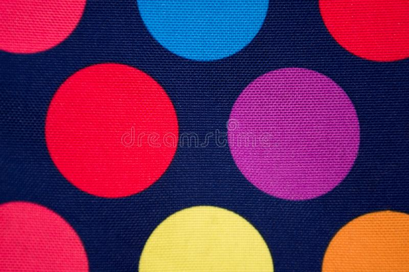 Dark blue fabric with colored circles. Background. texture royalty free stock photos