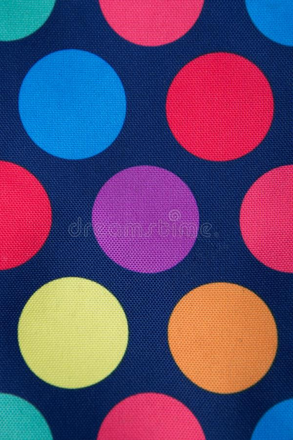 Dark blue fabric with colored circles. Background. texture stock photo