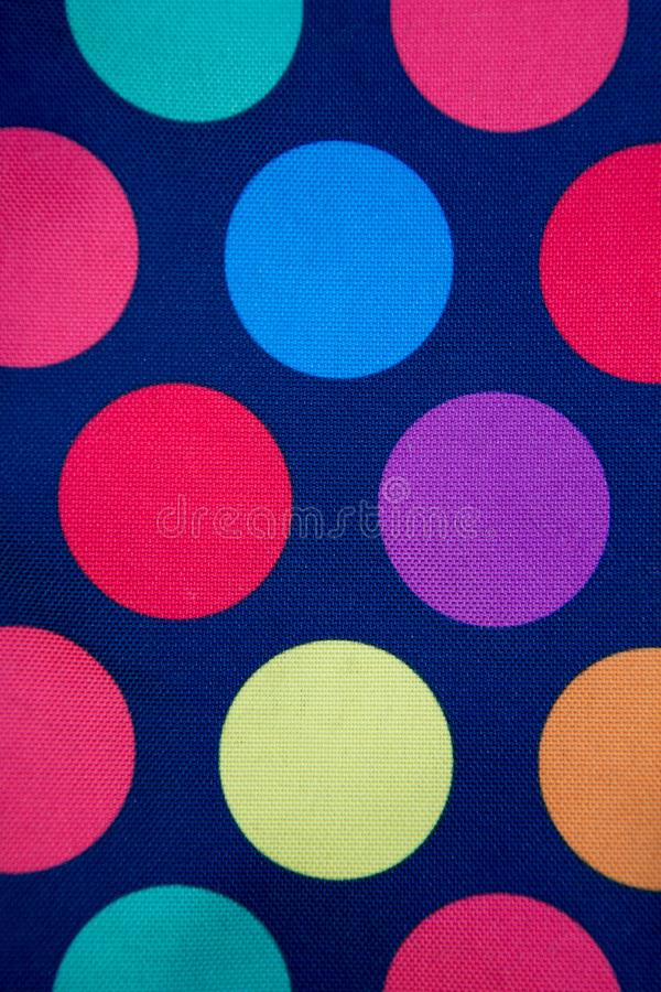 Dark blue fabric with colored circles. Background. texture royalty free stock photography