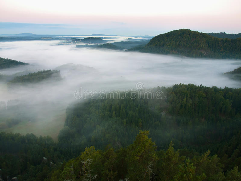 Dark blue fog in deep valley after rainy night. Rocky hill bellow view point. The fog is moving between hills and peaks of trees. Dark blue fog in deep valley stock photo