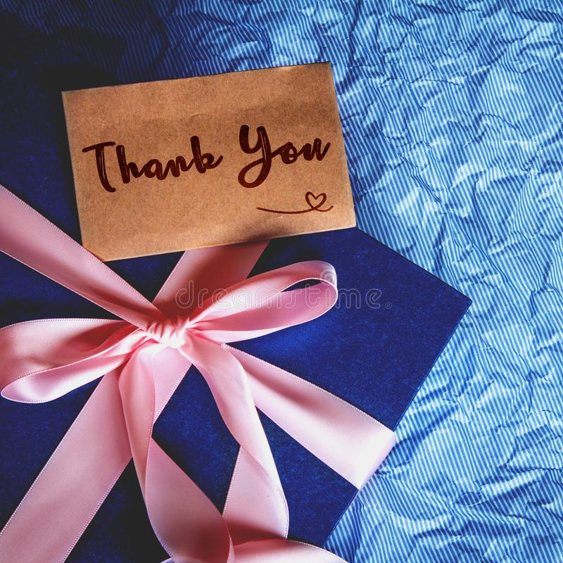 Dark blue gift box with ribbon decoration and Thank You card stock images
