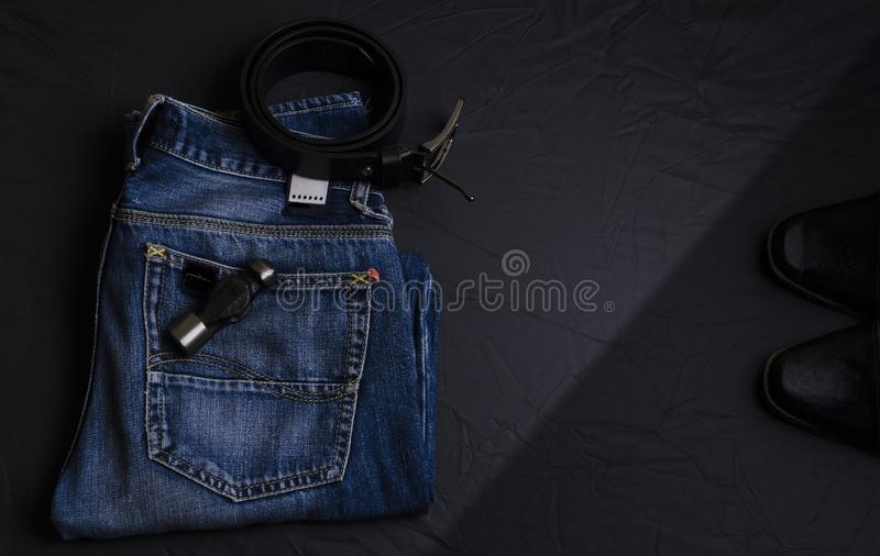 Dark blue jeans with a black leather belt and a pair of black shoes. Fashion accessories for men. Stylish dark blue jeans kept on dark background with a black stock photos