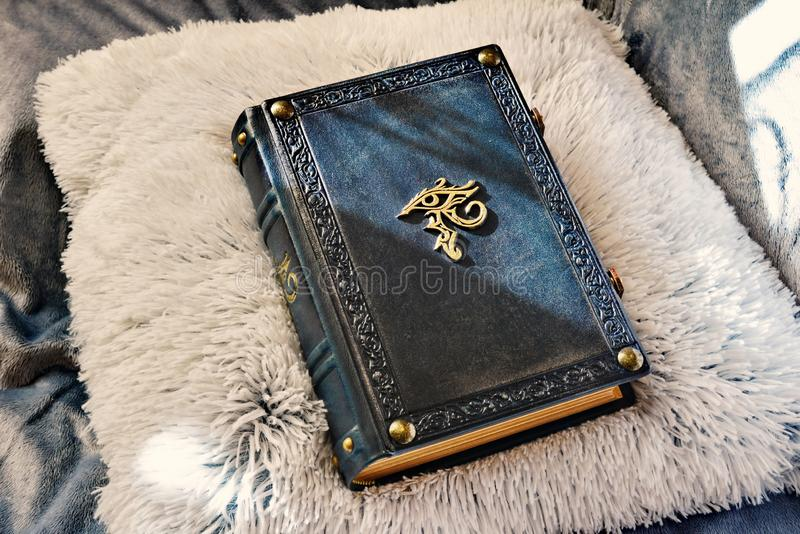 Dark blue leather book with the eye of Horus in the center of the front cover.  royalty free stock photos