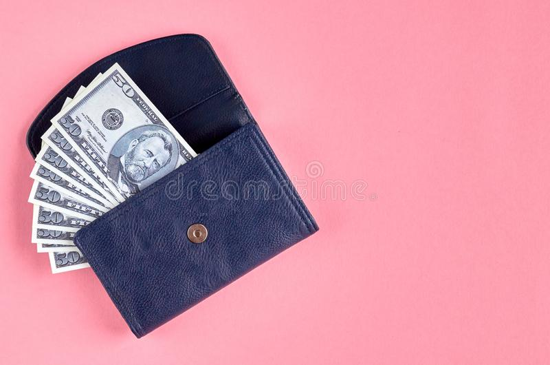 Dark blue leather wallet with money on pink background composition. Flat lay and top view photo, cash, dollar, purse, 50, layout, above, bright, card, concept stock photography