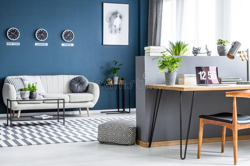 Dark blue living room interior with three clocks, simple poster, bright sofa and home office corner with laptop on hairpin desk royalty free stock photography