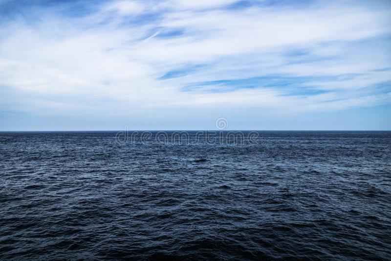Dark blue ocean water with sunny, cloudy sky in open water in South Korea stock photo