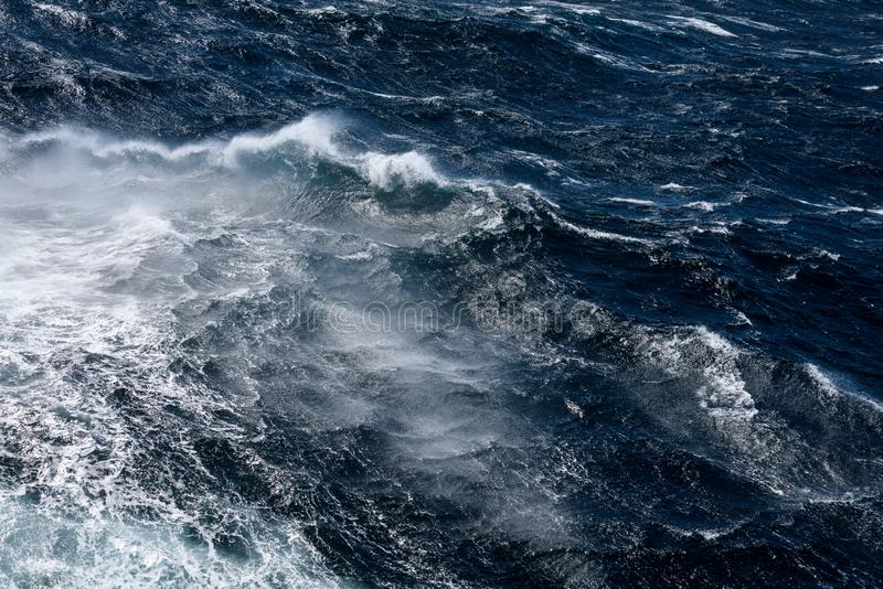Dark blue ocean water with waves and wind spray as a nature background royalty free stock photography
