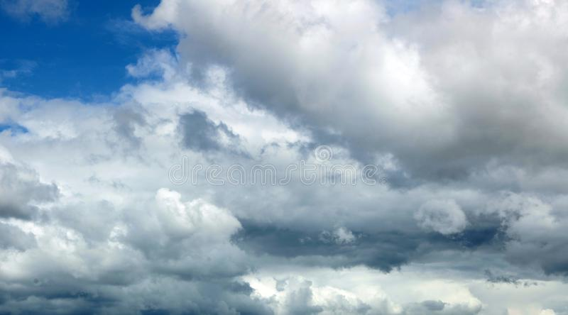 Blue ominous grey storm clouds. Dramatic white clouds at day time. Blue and white ominous grey storm clouds. Dramatic sky at day time. ecology comcept stock image