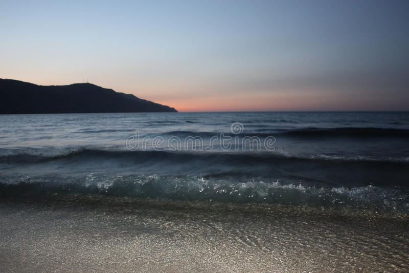 Dark blue sea waves over light sand with mountain and sunset on horizon royalty free stock photography