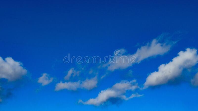 Dark Blue Skyscape White Grey Fluffy Clouds royalty free stock photo