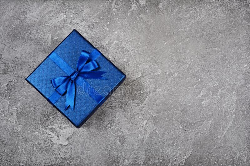 Dark blue square gift box with shiny satin bow royalty free stock photo