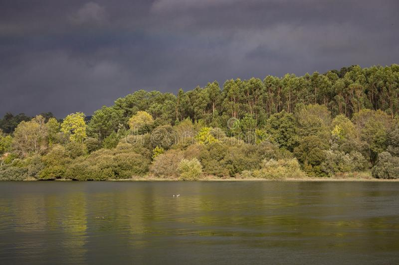Dark blue stormy sky over river and forest. Nature before storm. Beautiful river landscape. Meteorology and weather concept. royalty free stock image