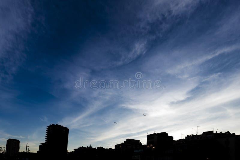 Dark blue sunset sky over skyscraper cityscape in Girona stock photos
