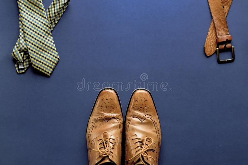 Dark blue surface with a belt. tie and shoes over it. A dark blue surface with a belt. tie and shoes over it stock photos