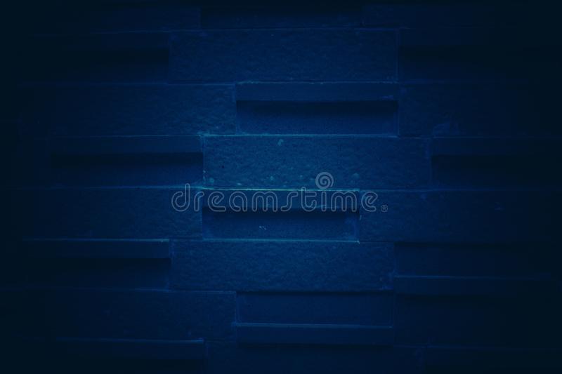 Dark blue tone background with patterned brick wall. For wallpapers stock image