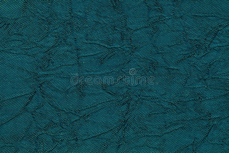 Dark blue wavy background from a textile material. Fabric with fold texture closeup. Creased shiny turquoise cloth royalty free stock image