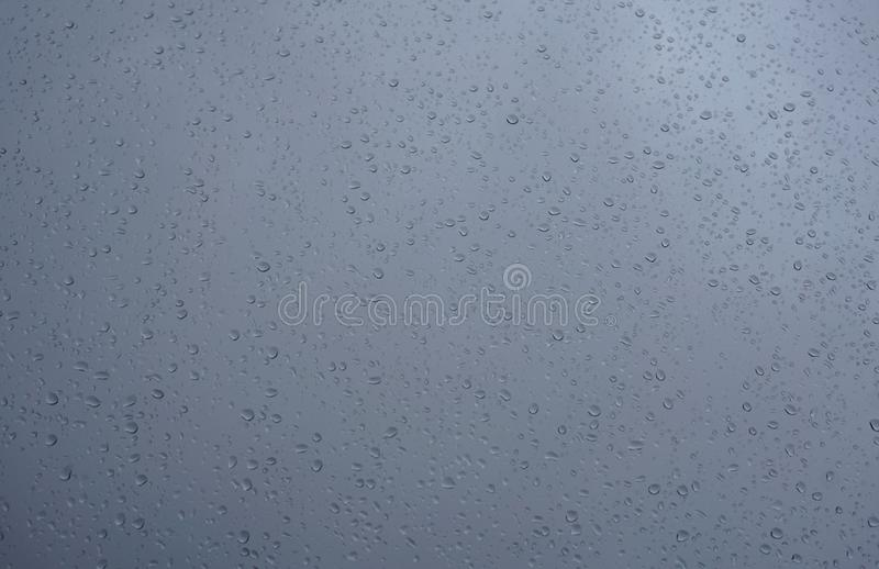 Dark blue window glass with rain drops on it. Water drips texture background royalty free stock photo