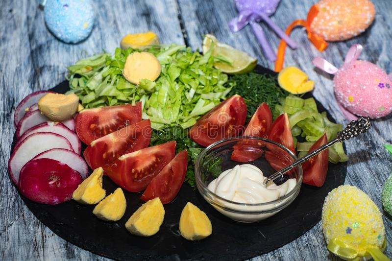 On a dark board lie oats sliced for salad. Tomatoes, radishes, cabbage, dill, celery, parsley, also stand in a transparent bowl sauce. Near stock images
