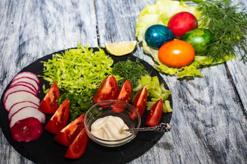 On a dark board lie oats sliced for salad. Tomatoes, radishes, cabbage, dill, celery, parsley, also stand in a transparent bowl sauce. Near royalty free stock image