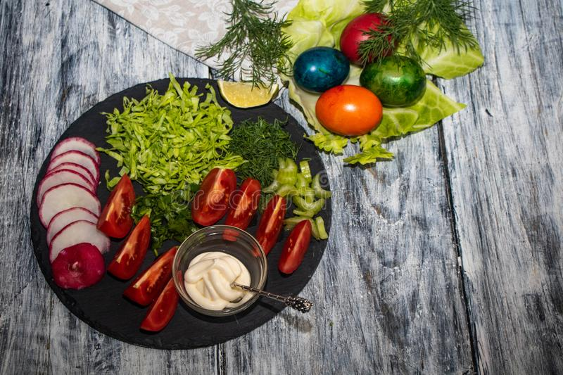 On a dark board lie oats sliced for salad. Tomatoes, radishes, cabbage, dill, celery, parsley, also stand in a transparent bowl sauce. Near stock image