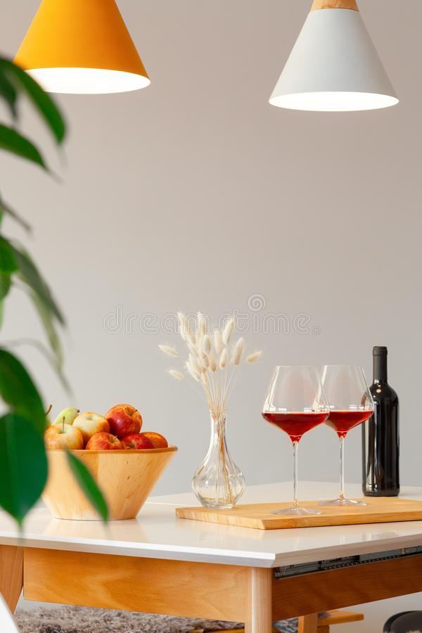 Dark bottle and two glasses of red wine, wooden bowl with apples, decor vase on table in modern kitchen, lamps over stock photos
