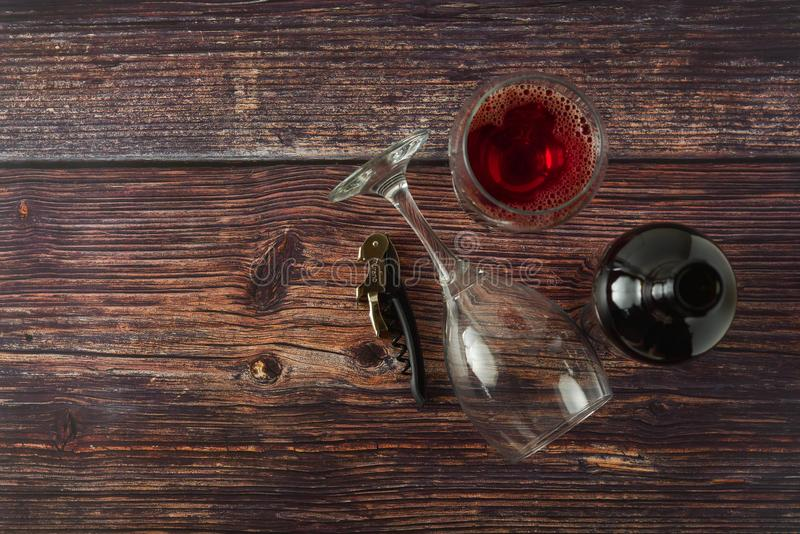Dark bottle of wine and glasses on wooden background. Top view with copy space. Dark bottle of wine and glasses on wooden background. Top view, copy space, party stock photo