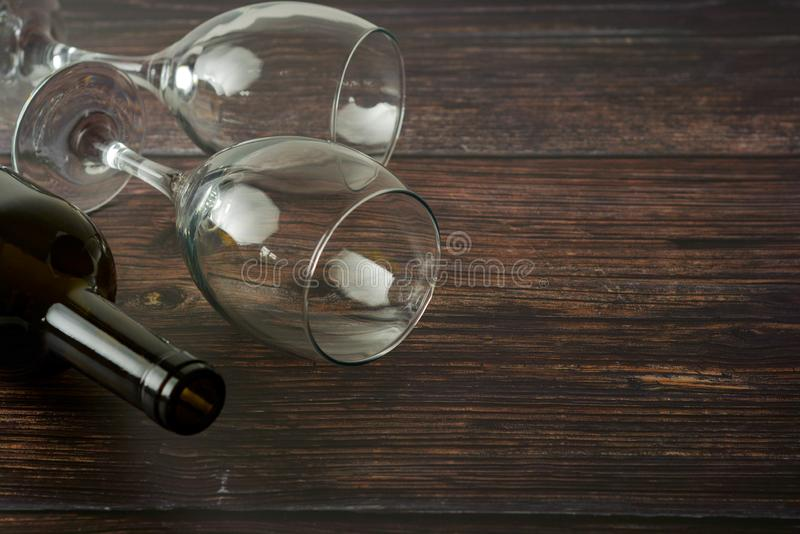 Dark bottle of wine and glasses on wooden background. Top view with copy space. Dark bottle of wine and glasses on wooden background. Top view, copy space, party stock photography