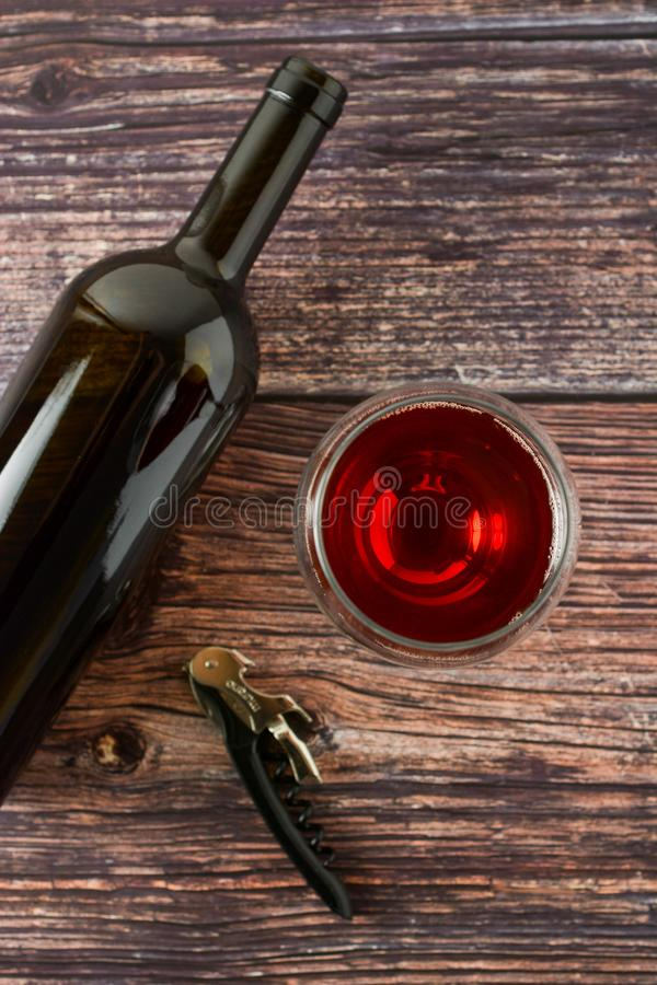Dark bottle of wine and glasses on wooden background. Top view with copy space. Dark bottle of wine and glasses on wooden background. Top view, copy space, party royalty free stock photo