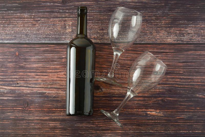 Dark bottle of wine and glasses on wooden background. Top view with copy space. Dark bottle of wine and glasses on wooden background. Top view, copy space, party stock photos