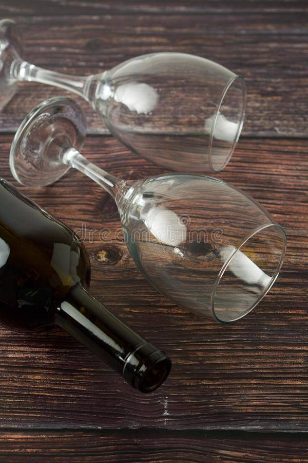 Dark bottle of wine and glasses on wooden background. Top view. Dark bottle of wine and glasses on wooden background. Flat lay, party, love, food, rose, vintage royalty free stock images