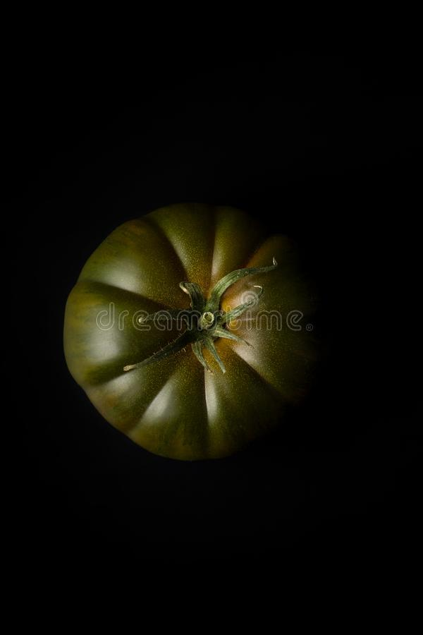 Dark brandywine tomato. On black background. Top view stock photos