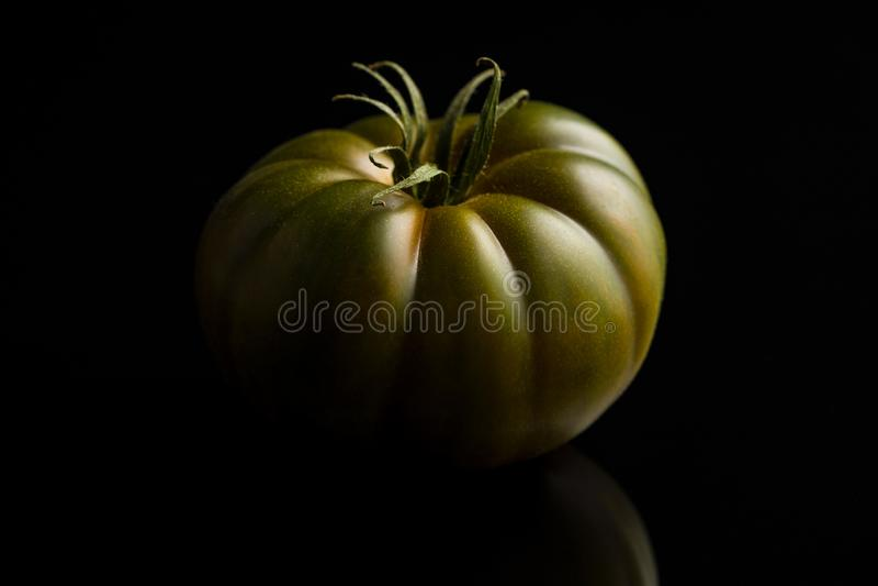 Dark brandywine tomato. On black background stock photo