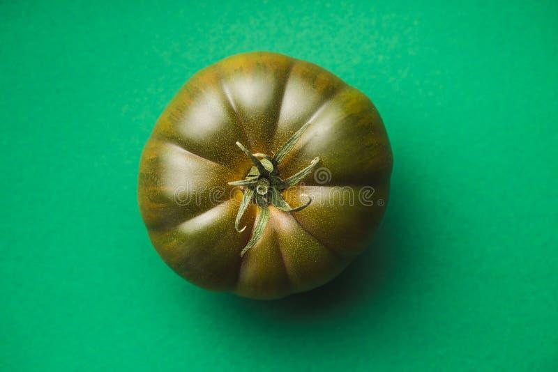 Dark brandywine tomato. On colorful background. Top view stock photos