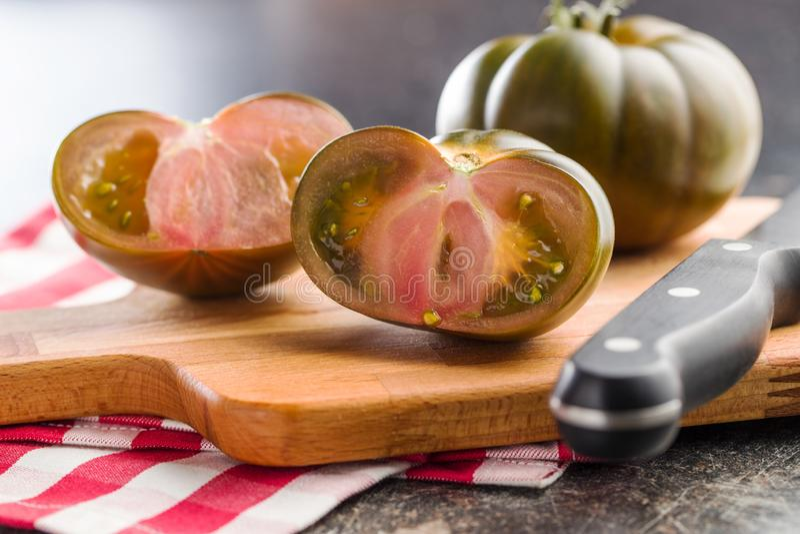 Dark brandywine tomatoes. On cutting board stock photography