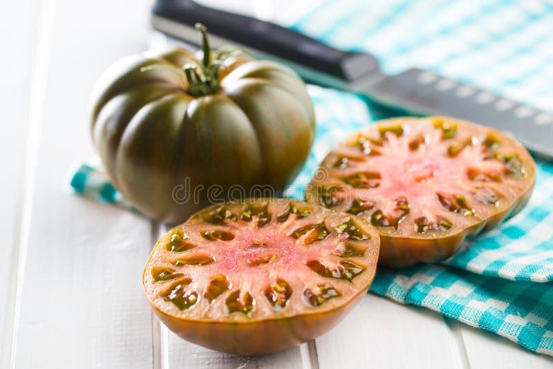 Dark brandywine tomatoes. On kitchen table stock photography