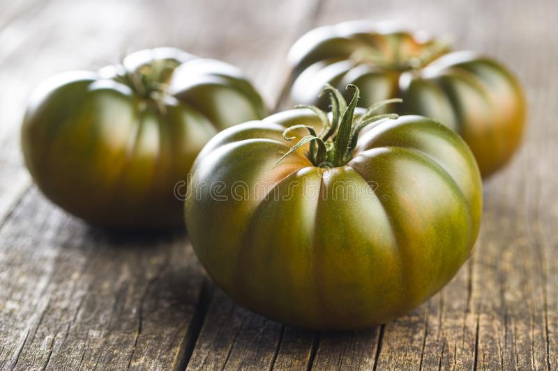 Dark brandywine tomatoes. On old wooden table stock photography