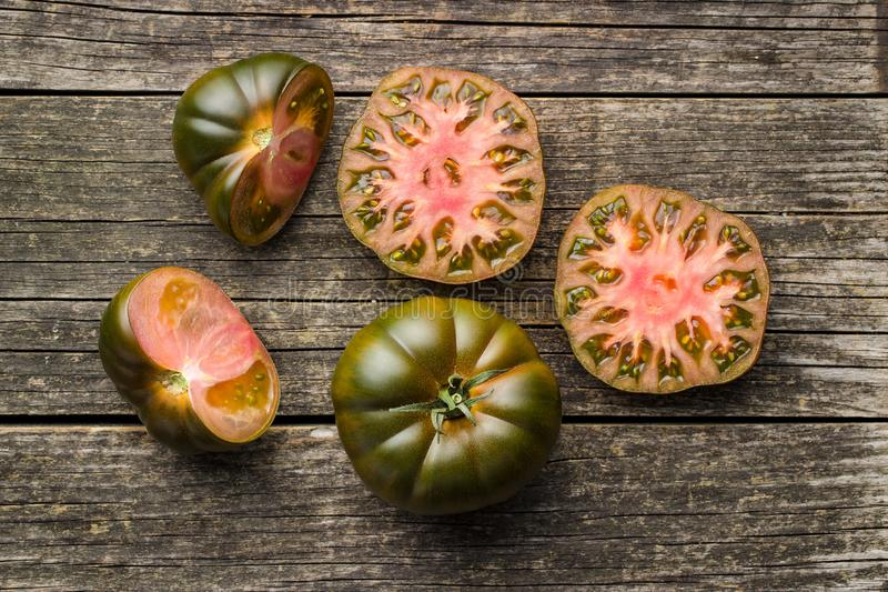 Dark brandywine tomatoes. On old wooden table. Top view stock images