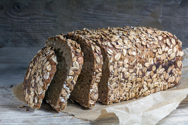 Dark bread loaf with whole grain and seeds on an old wooden boar. D stock image