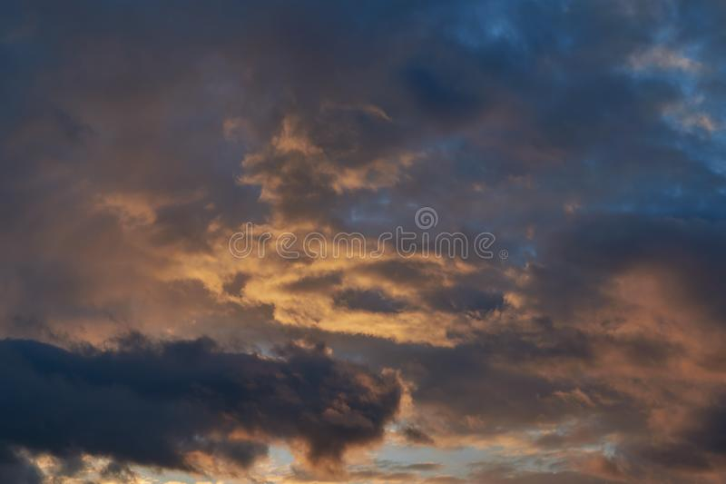 Dark and bright red Cumulus rain clouds illuminated by the evening sun stock photos