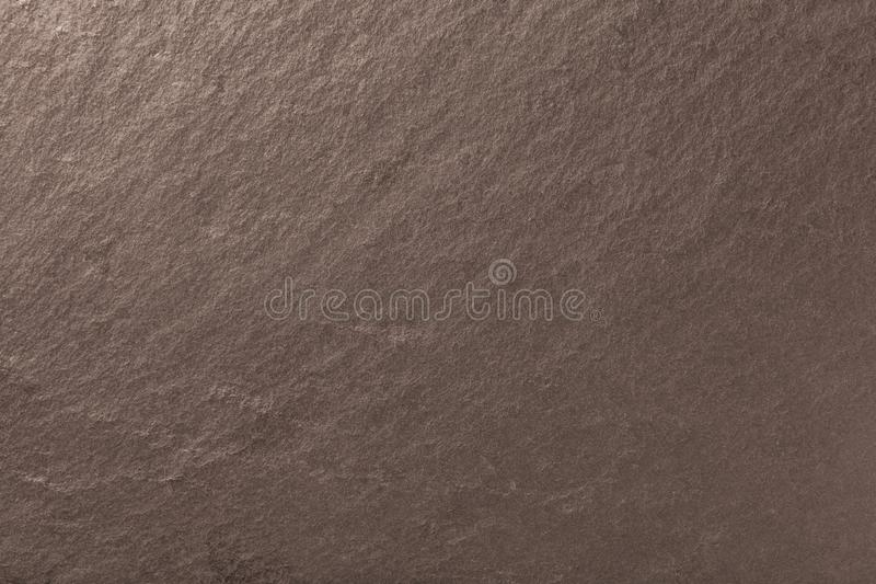 Dark bronze background of natural slate. Texture of stone. Dark bronze background of natural slate. Texture of brown stone closeup. Graphite backdrop macro stock image