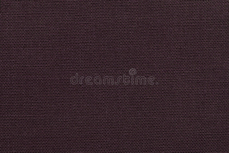 Dark brown background from a textile material with wicker pattern, closeup. stock photography