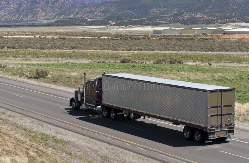 Dark brown classic American big rig semi truck transporting aluminum refrigerated semi trailer on the road in Utah. Dark brown classic American bonnet long haul stock photos