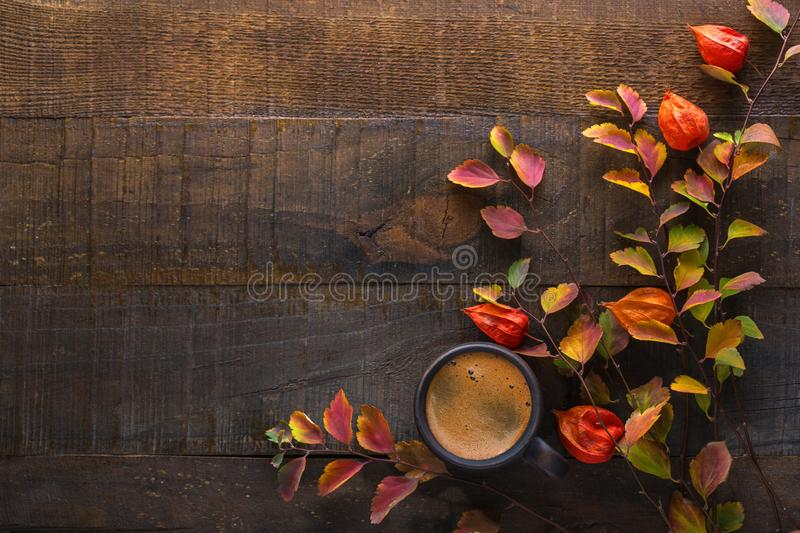 Dark brown clay cup with black coffee and branches of autumn leaves Spiraea Vanhouttei with Physalis on the old wooden table. To. P view stock photos