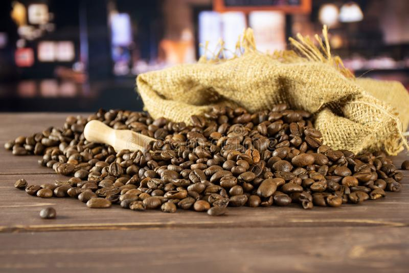Dark brown coffee beans sweet arabica with restaurant. Lot of whole dark brown coffee beans sweet arabica variety in a jute bag with restaurant in background stock photos