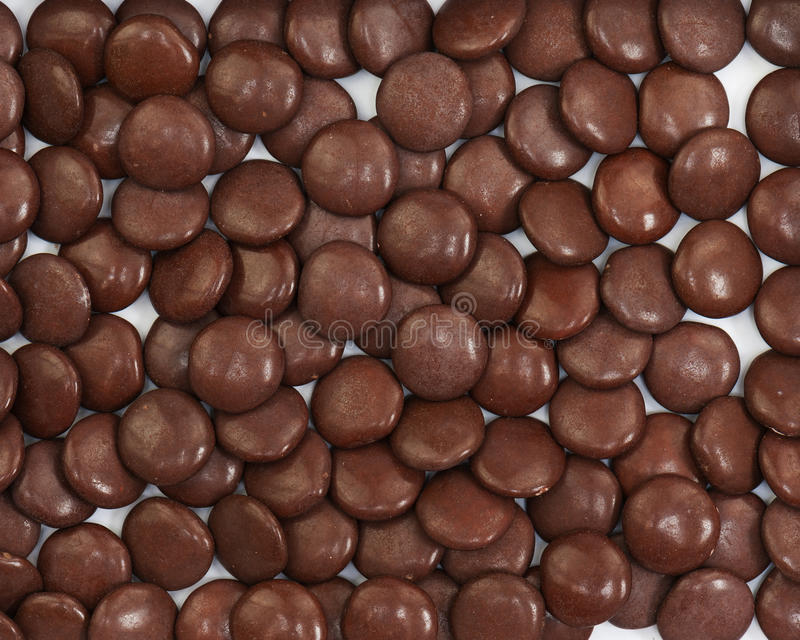 Dark brown dragee in chocolate covered. Whole background royalty free stock images