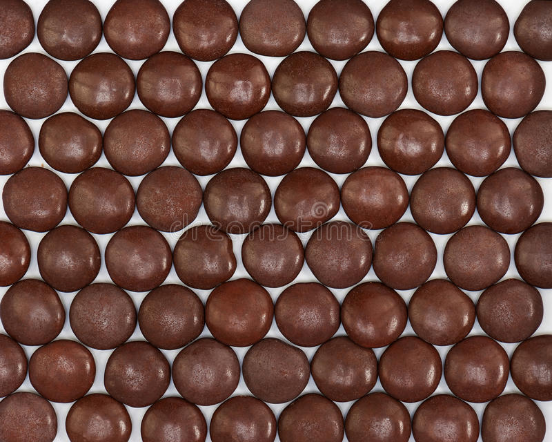 Dark brown dragee in chocolate covered. Whole background stock photo