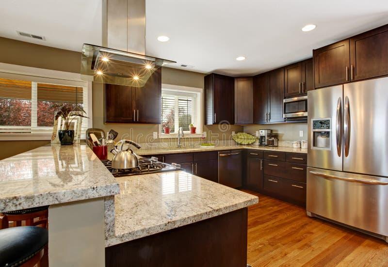 Dark brown kitchen room with steel appliances. And hardwood floor stock image