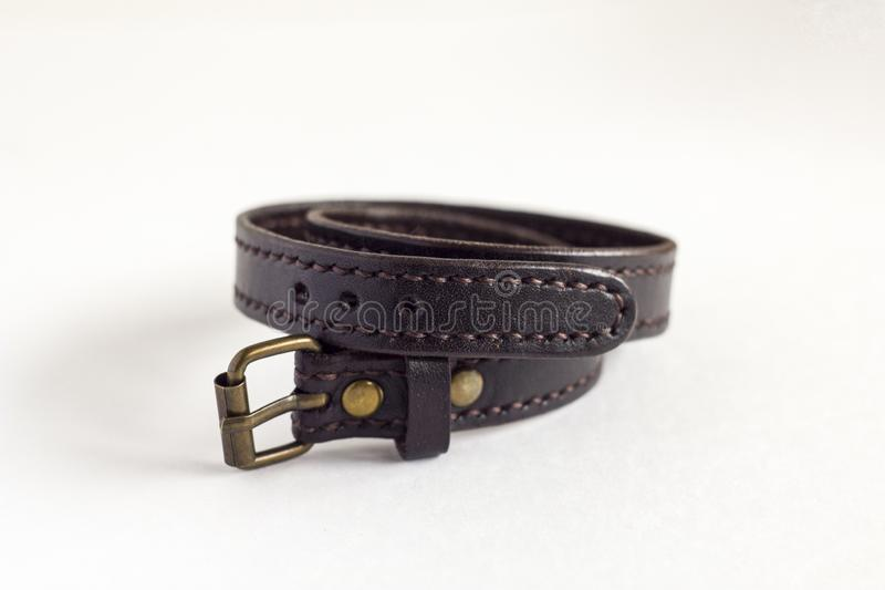 Dark brown leather stitched  bracelet isolated on white background. A dark brown leather stitched  bracelet isolated on white background royalty free stock photo